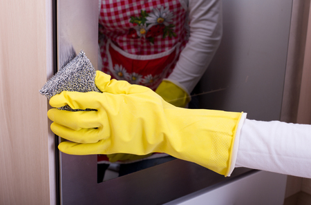 limpieza  del hogar: Close up of female hand with yellow protective gloves cleaning oven