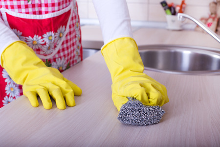 scrubbing: Close up of female hands with protective gloves scrubbing and cleaning kitchen countertop