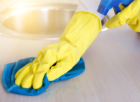 scrubbing up: Close up of female hands with protective gloves cleaning kitchen countertop