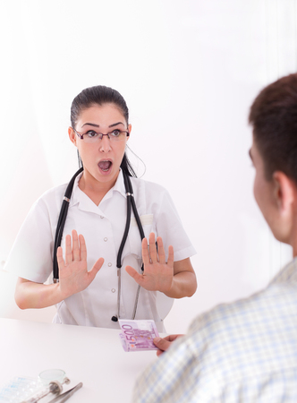 Young female doctor is shocked by patients bribing and she refusing money