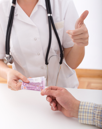 doctor money: Male patient giving money as bribing to young female doctor with thumb up Stock Photo