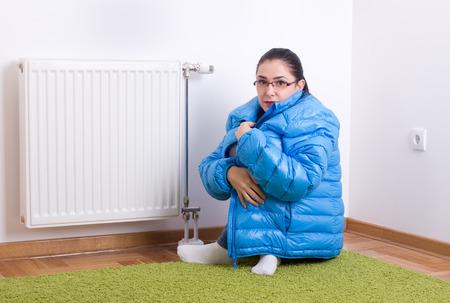 Jonge vrouw in blauwe winter jas zitten naast koude radiator Stockfoto