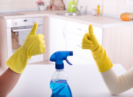 Close up of two workers gesturing ok sign after good job of cleaning in the kitchen Standard-Bild