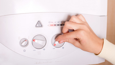 heat: Close up of female hand turning on gas boiler for heating water