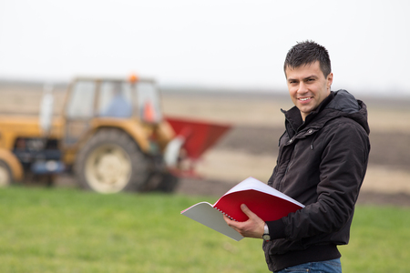 Young landowner with notebook supervising work on farmland, tractor sowing in background