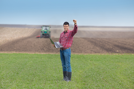 Satisfied landowner with laptop  holding fist up in the air on farmland, tractor plowing in background Archivio Fotografico