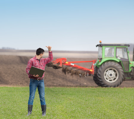 landowner: Satisfied landowner with laptop  showing thumb up to worker in tractor who plowing land