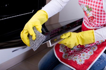 limpieza  del hogar: Primer plano de la mano femenina con guantes amarillos limpieza del horno Foto de archivo