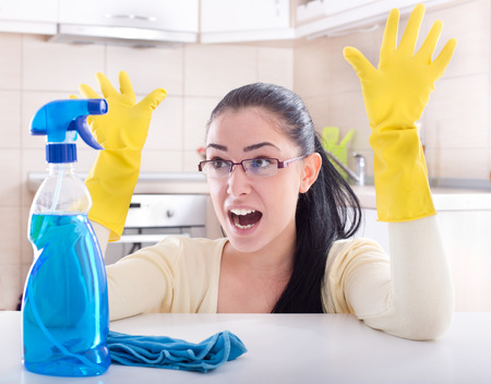 Frustrated young woman over house cleaning. Spraying bottle and mop on the table in front of her and kitchen in background Zdjęcie Seryjne