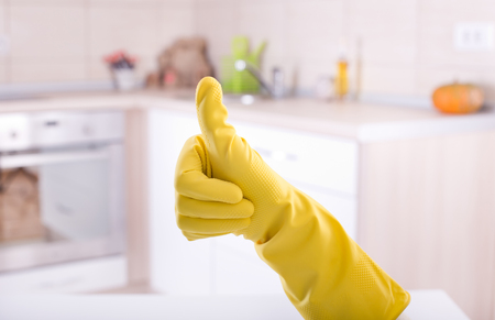 Conceptual image of home cleaning. Close up of human hand with yellow rubber glove showing ok sign with thumb up. Cleaned kitchen in background