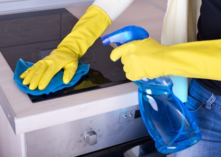 house interior: Close up of female hands with rubber gloves holding mop and spray bottle and cleaning cooker Stock Photo