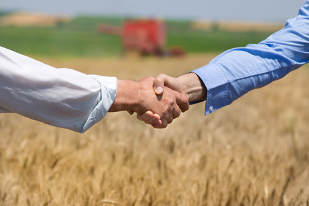 harvest: Close up of two businessmen shaking hands on the farmland. Combine harvester working in background