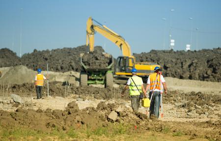 Trabajadores de la construcción que llevan equipos de nivelación en el sitio de construcción de carreteras, camiones excavadora de carga en segundo plano Foto de archivo