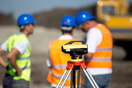 leveling instrument: Theodolite on tripod at road construction site with workers supervising works in background