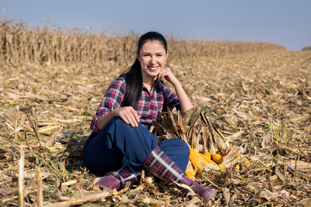 cereals holding hands: Young smiling girl sitting on harvested field with corn cobs beside her