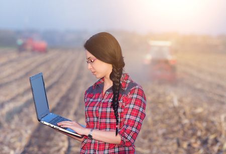 agronomist: Young woman agronomist standing on field with laptop. Tractors working in background