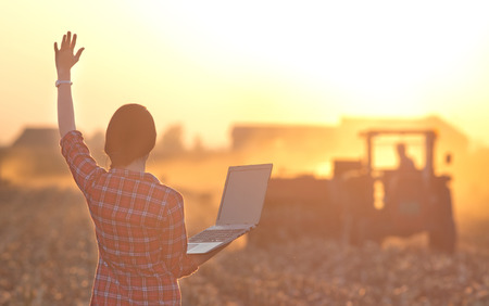 Young woman with laptop standing on field and waving hand to a tractor driver in sunset