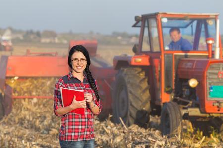 granjero: Agricultora joven que se coloca en campo de ma�z durante el empacado. Tractor en el fondo