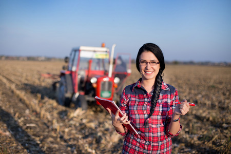 Young woman farmer standing on corn field during baling. Tractor in background