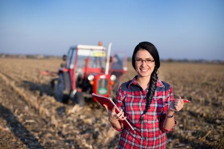 Jonge boerin staande op maïsveld tijdens het persen. Tractor op de achtergrond