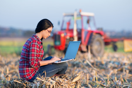 mujer trabajadora: Mujer joven con ordenador portátil sentado en la bala en el campo. Tractor en el fondo Foto de archivo