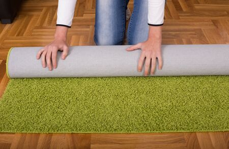 rolling up: Close up of female hands rolling green fluffy carpet for cleaning