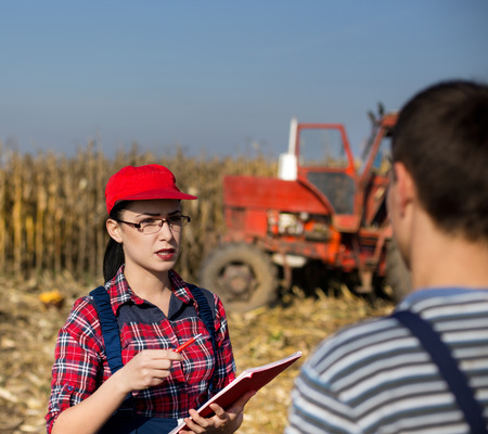 quality controller: Young female quality controller talking to a farmer on corn field during harvest
