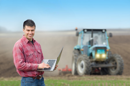 engineer computer: Young landowner with laptop supervising work on farmland, tractor plowing in background