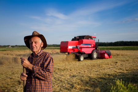 campesino: Sonriendo viejo campesino de pie en el campo con combinar en segundo plano