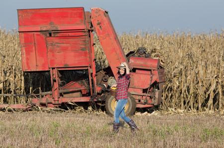 elote: Chica agricultor joven que sostiene la cesta con la mazorca de maíz en el campo. Maquinaria agrícola trabajan en segundo plano