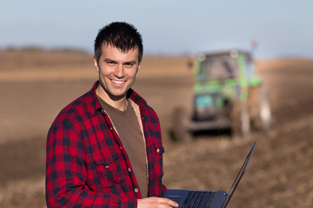 landowner: Young landowner with laptop supervising work on farmland, tractor plowing in background