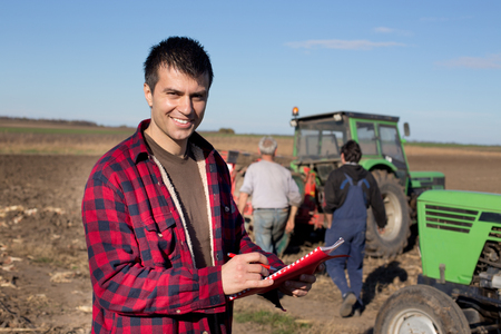landowner: Young handsome farmer standing on farmland. Workers and tractors in background