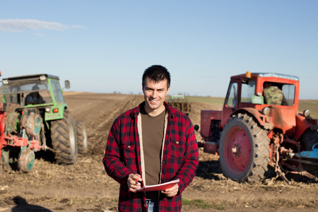 landowner: Portrait of young handsome farmer on farmland. Tractors working in background