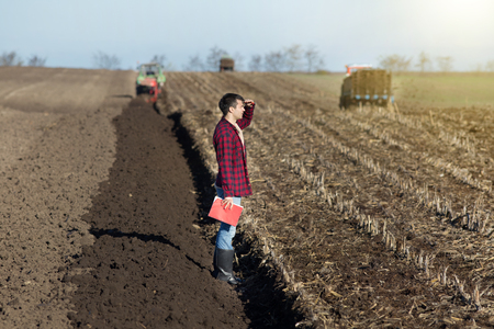 landowner: Young handsome farmer standing on farmland. Tractors working in background