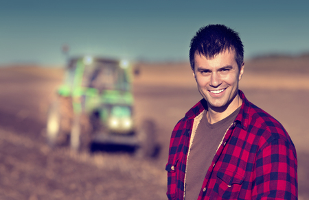 Portrait of young handsome farmer on farmland. Tractor working in background