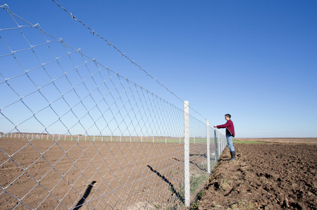 barbed wire fence: Young man holding barbed wire fence and looking ahead