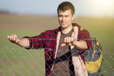 Young desperate man with backpack holding barbed wire fence and looking ahead Фото со стока