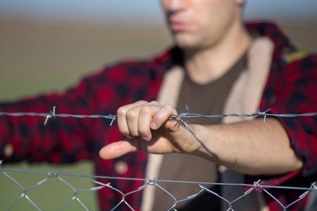 有刺鉄線の柵を持っている男性の手のクローズ アップ 写真素材