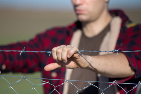 Close up of male hand holding barbed wire fence