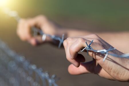 illegal immigrant: Close up of male hands holding barbed wire fence and begging for help