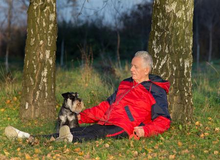 amigos abrazandose: Hombre mayor con su perro schnauzer miniatura que se sienta en la hierba en el bosque