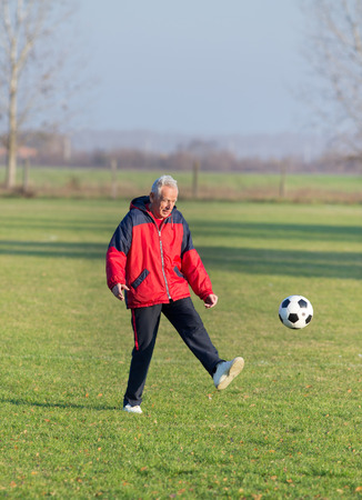 the seventies: Old man in seventies kicking a soccer ball on the grass field
