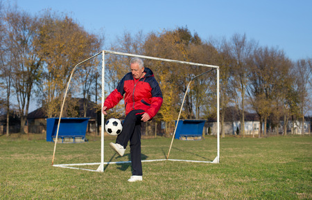 active people: Old man in seventies kicking a soccer ball on playground with goal behind him