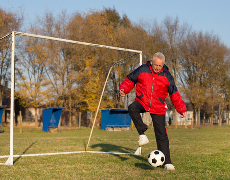 the seventies: Old man in seventies kicking a soccer ball on playground with goal behind him