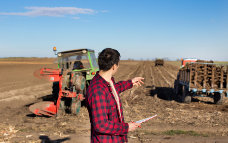 fertilizing: Young handsome farmer standing on farmland and showing tractor that fertilizing land Stock Photo