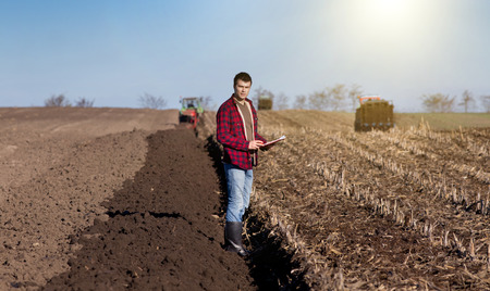 fertile land: Young handsome farmer standing on farmland. Tractors working in background
