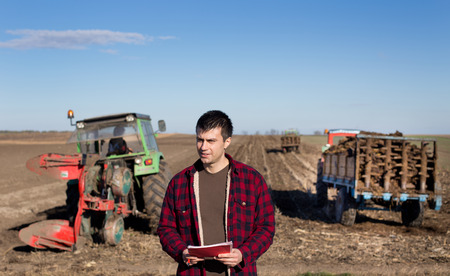 fertile land: Portrait of young handsome farmer on farmland. Tractors working in background