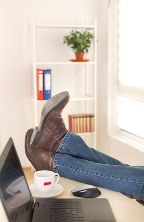 office shoes: Close up of male legs in shoes on office desk with laptop and cup of coffee beside