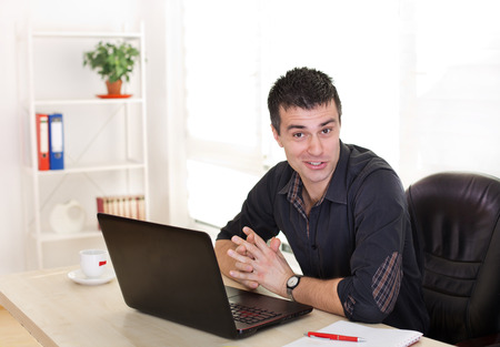 astounded: Young businessman making funny faces in the office. Sitting at desk with laptop Stock Photo
