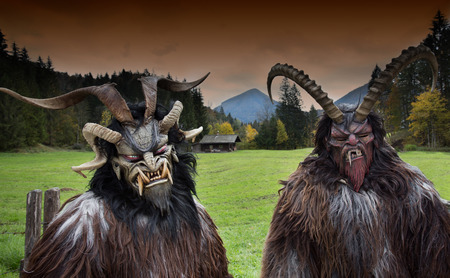 scary face: Two men wearing traditional Krampus beast-like mask from Alpine region Stock Photo